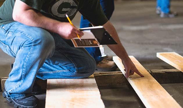 northern hardwoods employee checking plank quality